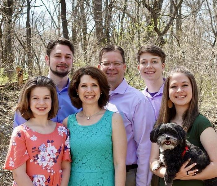 Tim and April Howell, are pictured with their four kids and their dog, Bentley.